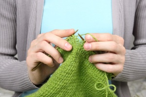 woman knitting green threads closeup